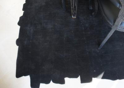 Tapis avec insertions de fils métalliques pour accompagner les éléments en métal de la table et structurer le tapis selon le mobilier.